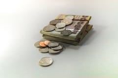 Soldi tailandesi, 1000 banconote di baht e moneta su fondo bianco Fotografia Stock