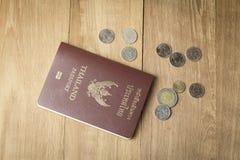 Soldi tailandesi della moneta e del passaporto su fondo di legno Immagine Stock