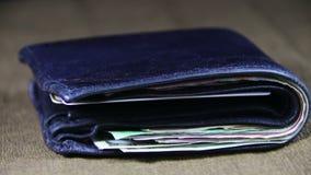 Soldi in un portafoglio che gira su una Tabella di legno archivi video