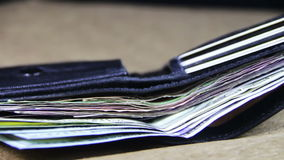 Soldi in un portafoglio che gira su una Tabella di legno video d archivio