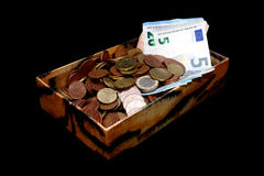 Soldi in una vecchia scatola, in banconote ed in monete, isolate sul nero Fotografia Stock