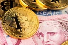 Soldi virtuali di cryptocurrency di Bitcoin sulle banconote reali brasiliane dei soldi immagine stock