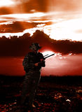 Soldier. With gun in blood red land with sunset Stock Photography