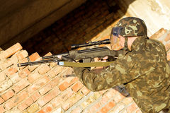 Soldier. Assaulting near the red brick wall stock photo