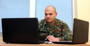Soldier. A soldier working on laptop in office looking at the monitor royalty free stock photo