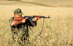 Soldier. A soldier aiming his assault-rifle in a field royalty free stock images