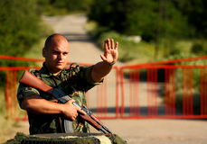 Soldier. Making stop sign in-front of a gate holding assault rifle (AK-47 Stock Image