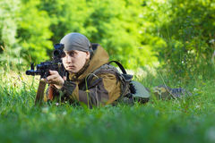 Soldier. In camouflage with a Kalashnikov assault rifle lying on the grass royalty free stock photos