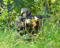 Soldier. In camouflage with a Kalashnikov assault rifle, shooting in the woods stock photo