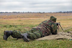 Soldier. In camouflage uniforms with machine gun lying on the grass and fights royalty free stock photography