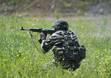 Soldier in action. Firing his automatic rifle kalashnikov Royalty Free Stock Images