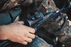 A soldier adjusts optical sight on a rifle. Stock Photos