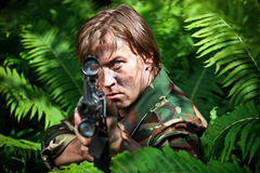 Soldier aiming a gun. Soldier hiding in a bushes and aiming a gun Royalty Free Stock Images