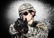 Soldier aiming a gun. USA soldier aiming a gun on gray background stock photos