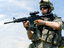 Soldier aiming his rifle. Soldier in camouflage uniform aiming his rifle royalty free stock image
