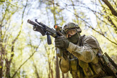 Soldier aiming holding submachine gun. In forest on mission stock images