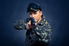Soldier aiming a machine gun on a blue background. With a focus on the barrel machine Stock Photography
