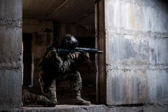 Soldier aiming a rifle in ruins. Armed soldier in camouflage, mask and helmet aiming a rifle in a dark room royalty free stock image