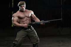 Soldier Aims Machine Gun. Action Hero Muscled Man Holding Machine Gun - Standing In Abandoned Building Wearing Green Pants Stock Photo