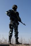 Soldier with a AK-47 rifle on guard. Armed officer in full combat ammunition standing on guard Royalty Free Stock Photo
