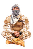 Soldier with  arabian scarf  covering his face, sitting cross- l. Egged  on white background Stock Image