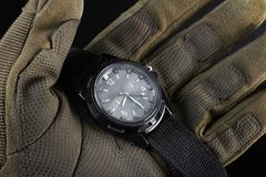 Soldier arm holding black tactical watch close up