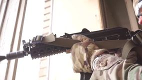 Soldier armed with an assault rifle guarding room near the broken window stock video footage