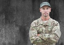 Soldier with arms folded against black wood panel with grunge overlay Royalty Free Stock Image