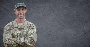 Soldier arms folded against grey background with grunge overlay Stock Photos
