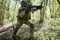 Soldier with arms on task. In woods during day Royalty Free Stock Image