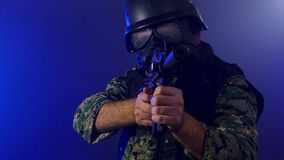 Soldier holding assault rifle in smoky haze. Soldier in army fatigues wearing gas mask holding assault rifle in haze of blue smoke stock footage