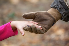 A soldier in the army uniform and gloves, holding out his hand a little girl. Royalty Free Stock Photo