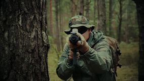 Soldier with assault rifle and a backpack on a patrol. In the woods stock footage