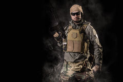 Soldier with an assault rifle. Special Forces soldier with an assault rifle on a black background Stock Photography