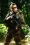 The soldier with automatic rifle. In a forest stock photos