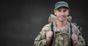Soldier with backpack against grey wall stock images