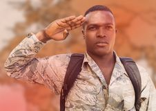 Soldier with backpack saluting against blurry brown map and red overlay Royalty Free Stock Image