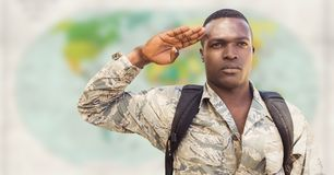 Soldier with backpack saluting against blurry map Royalty Free Stock Photos
