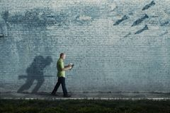 Soldier and battle. A man walks with a soldier shadow running towards battle royalty free stock photos