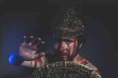 Soldier, bearded man warrior with metal helmet and shield, wild Stock Images