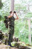 Soldier with binocular and backpack in forest Stock Photography