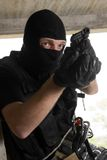 Soldier in black mask with 9mm pistol. Photo of armed man in combat uniform playing terrorist or special forces team member Stock Photos
