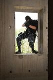 Soldier in black mask entering through the window Stock Images