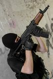 Soldier in black mask moving upstairs with rifle Stock Images