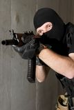 Soldier in black mask targeting with AK-47 rifle Stock Image