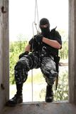 Soldier in black mask wntering the window on rope Royalty Free Stock Photos