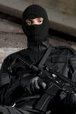Soldier in black uniform with a gun Stock Image