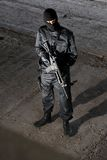 Soldier in black uniform with M-4 rifle. Trooper in black camouflage holding a gun Royalty Free Stock Images