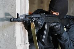 Soldier in black uniform with rifle. Gunman aiming his target with an automatic russian AK-47 rifle Royalty Free Stock Image