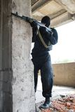 Soldier in black uniform with rifle. Gunman aiming his target with an automatic russian AK-47 rifle Royalty Free Stock Images